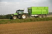 [Deutz-Fahr] trattore Agrotron K 110 con rimorchio su una strada di campagna