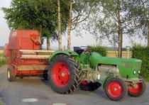 [Deutz] trattore D 8006 con rotopressa Fahr su una strada di campagna